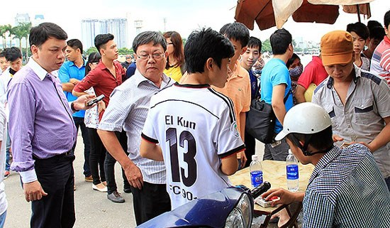Vietnam Football Federation's (VFF) General Secretary Le Hoai Anh (L) inspects a ticket booth for the Nutifood U19 Cup 2014 in Hanoi. Photo credit: VFF