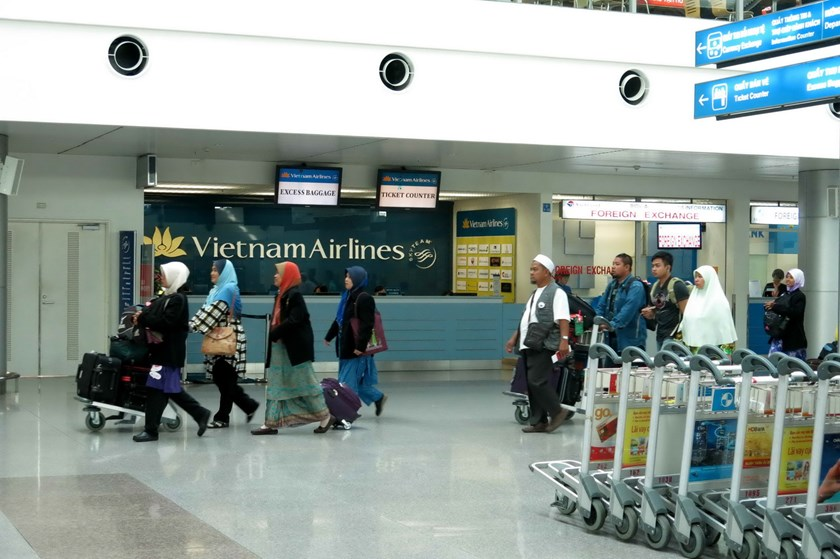 Passengers pass a Vietnam Airlines counter at Ho Chi Minh City's Tan Son Nhat Airport. Photo: Kha Hoa