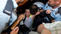 A protester is taken away by police officers after staying overnight at Hong Kong's financial Central district, in this July 2, 2014 file picture. Photo credit: Reuters