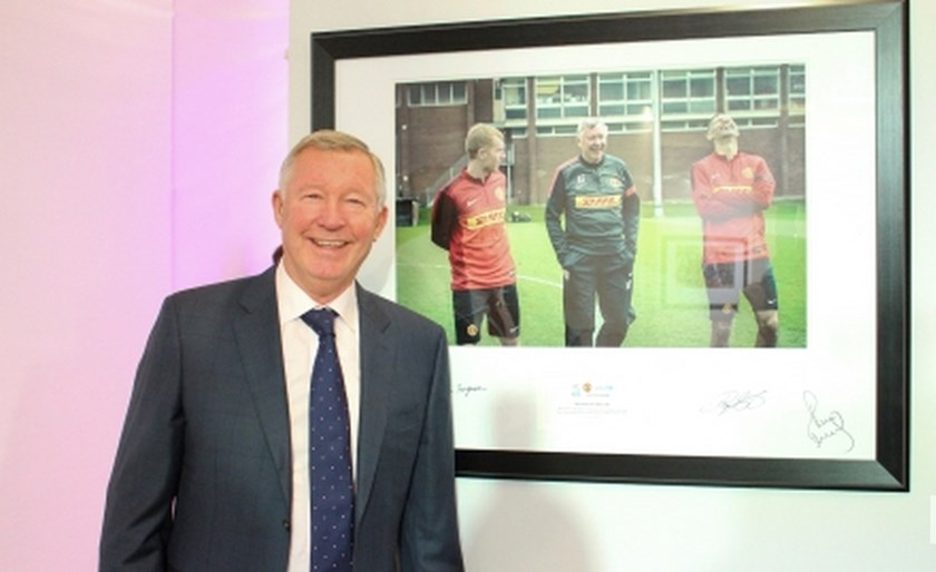 Alex Ferguson stands by a picture at the exhibition.