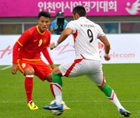 Vietnam's Mac Hong Quan (R) vies for the ball with an Iranian player at their qualifying match at the Asian Games 2014. Photo: Quang Tuyen