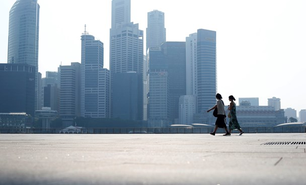 People walk past the skyline of the financial district on a hazy day in Singapore September 4. Photo credit: Reuters