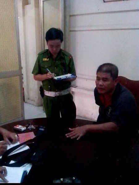 Nguyen Ngoc Thong (R) being interrogated at a police station. Photo: Dam Huy