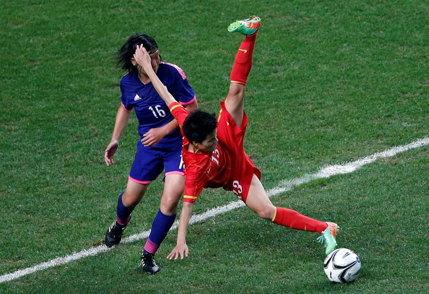 Japan's Hisui Haza (L) and Vietnam's Thi Muon Nguyen fight for the ball during their women's semi-final soccer match at the Incheon Football Stadium during the 17th Asian Games in Incheon September 29, 2014.. Photo credit: Reuters