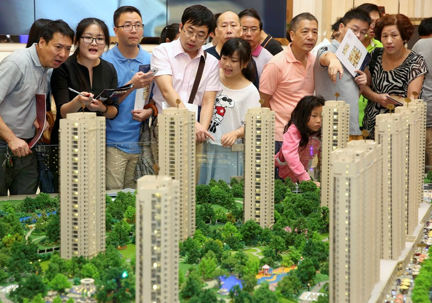 Customers look at a model of a new residential compound, at a showroom of Longfor Properties Co. Ltd., in Hangzhou, Zhejiang province in this August 17. Photo credit: Reuters
