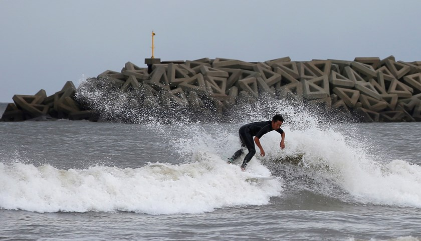 A surfer rides a wave as Typhoon Phanfone passes the area, at a beach in Tsu, Mie prefecture, October 6, 2014. Hundreds of flights were cancelled and thousands of people advised to evacuate as a powerful typhoon lashed Japan on Monday with heavy rains and