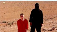 A masked man stands next to a kneeling man identified as U.S. citizen Peter Edward Kassig (L), in this still image taken from video released by Islamic State militants fighting in Iraq and Syria, on October 3. Photo credit: Reuters