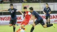Van Long (C) vies for the ball with two Singapore players during a match in Thanh Nien Newspaper's 2014 U21 International Football Tournament in Can Tho City on Sunday. Vietnam crushed Singapore 3-0 in the first match of the tournament. Photo: Kha Hoa