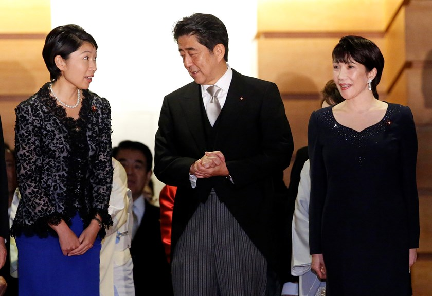 Japan's Prime Minister Shinzo Abe (C) talks with Economy, Trade and Industry Minister Yuko Obuchi (L) and Internal Affairs and Communications Minister Sanae Takaichi as they prepare for a photo session at his official residence in Tokyo in this September