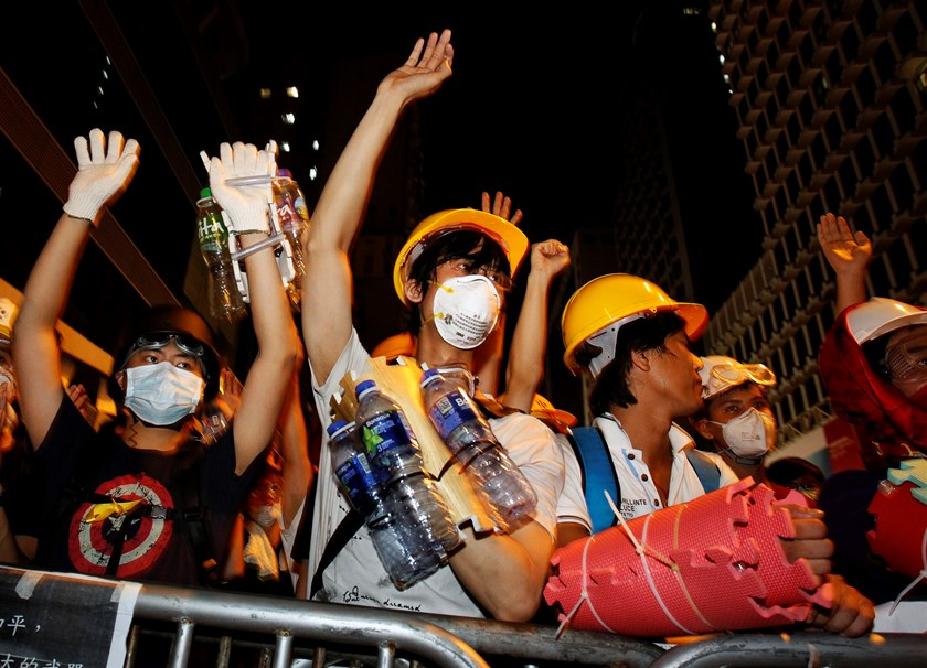 Pro-democracy protesters, protecting themselves with helmets, masks, foam pads and empty plastic bottles, raise their hands at riot police as a gesture of peace after they were told by visiting lawmakers not to charge the police defence line, at Mongkok s