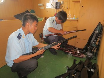 Customs officers inspect pellet guns seized from a cargo ship. Photo: Nguyen Long