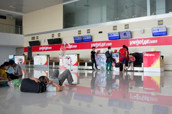 A passenger uses a mobile phone as he lies near a check in counter for VietJet Air, operated by VietJet Aviation Joint Stock Co., at Noi Bai International Airport in Hanoi, Vietnam, on Sunday, June 1. Photo credit: Bloomberg