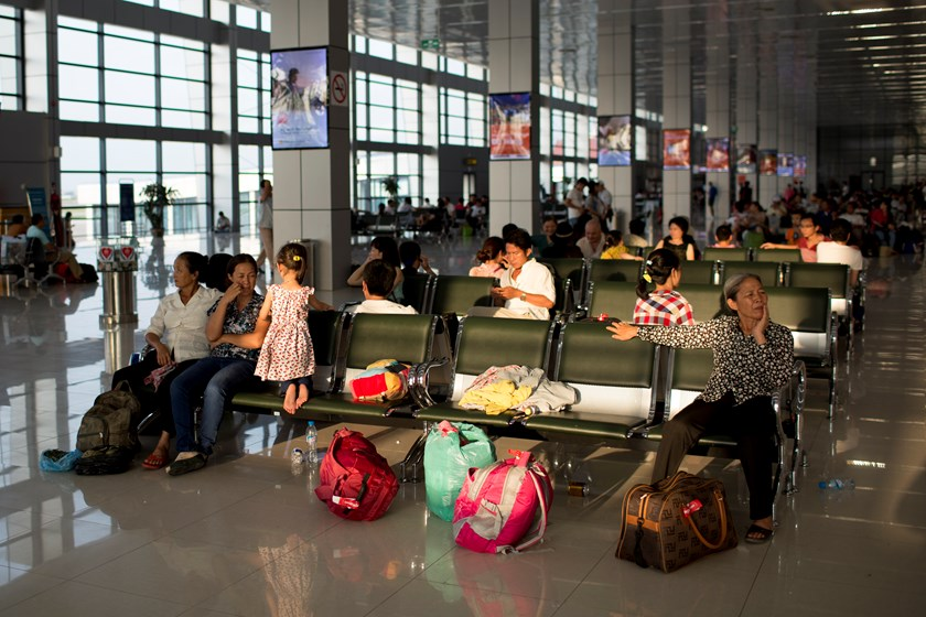 Passengers sit inside a departure lounge at Noi Bai International Airport in Hanoi, Vietnam. Photo credit: Bloomberg