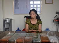 Mai Quynh Tho at the police station with the 13 bricks of heroin seized from her home. Photo: Hoang Long