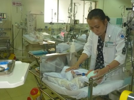 A nurse cares for a newborn baby who was delivered after his mother was killed in an accident on October 25. His father survived with a broken leg and doctors had to amputate a limb from the baby. File photo