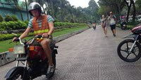 A foreigner learns how to drive a motorbike on the sidewalk of Pham Ngu Lao Street in downtown Ho Chi Minh City. Photo: Dam Huy