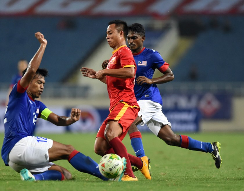 Vietnam's Tien Thanh (C) vies for the ball with two Malaysian players during a friendly match at Hanoi's My Dinh Stadium on November 16. Photo: Ngo Nguyen