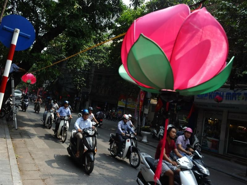 Motorcyclists ride on a Hanoi street decorated with lotus-shapped lanterns hanging over a street in Hanoi. Photo credit: AFP