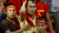 A Vietnamese fan wipes blood on his head after being attacked by local fans during the first leg of the Suzuki Cup 2014 semi-final match between Vietnam and Malaysia at Shah Alam Stadium in Kuala Lumpur on December 7. Photo credit: Reuters