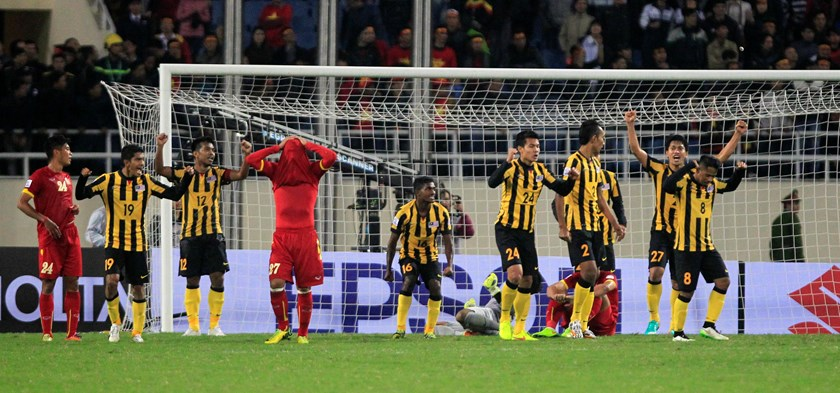 Malaysia's players (in yellow) celebrate their victory against Vietnam after the second leg of their ASEAN Football Federation Suzuki Cup 2014 semi-final soccer match at My Dinh stadium in Hanoi December 11, 2014. Photo credit: Reuters