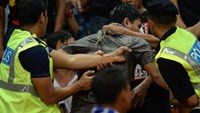 This photo taken on Dec 7, 2014 shows Malaysian police arresting a football fan (C) during the AFF Suzuki Cup 2014 first leg semi-final football match between Malaysia and Vietnam at the Shah Alam Stadium in Shah Alam, outside Kuala Lumpur. Photo credit: