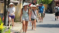 Foreign tourists stroll down a street in Hoi An Town. Photo: Hoang Son
