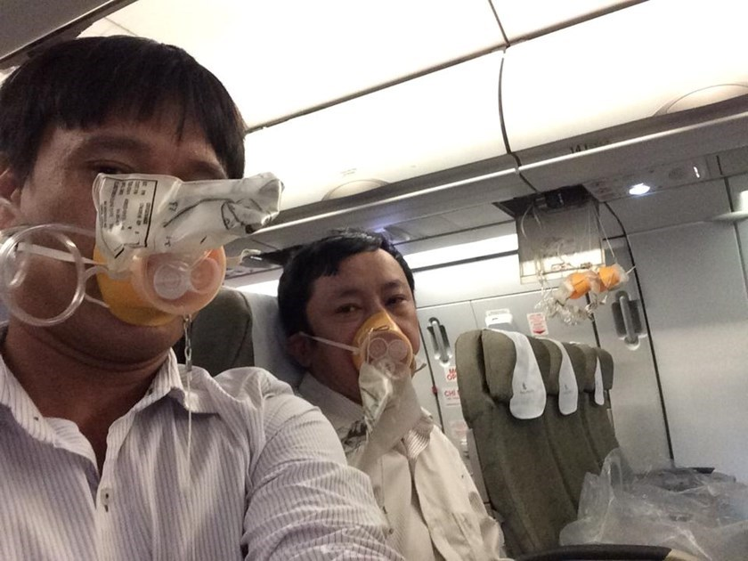 Passengers on board a Vietnam Airlines flight don oxygen masks after technical problems led to a sudden drop in cabin pressure on December 16, 2014. Photo via a passenger's Facebook page