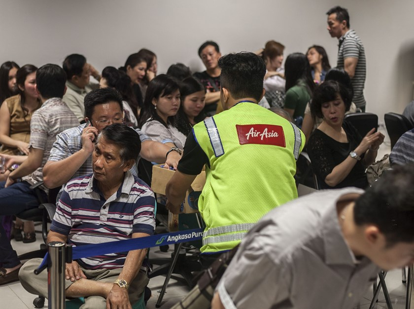 Family members of passengers from missing Malaysian air carrier Air Asia flight QZ8501 gather at the airport in Surabaya, East Java, on December 28, as they await news of their relatives. Photo credit: AFP