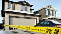 Police tape cordons an area around the home where seven persons were found dead in Edmonton, Alberta, December 31, 2014. Photo credit: Reuters