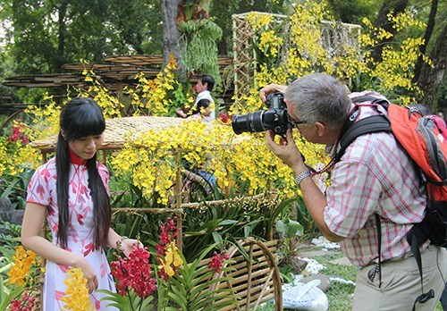 A foreign tourist taking photo of a Vietnamese girl in traditional ao dai (Vietnamese dress) at the 2014 Spring Flower Festival in Ho Chi Minh City. Photo: Nguyen Mi
