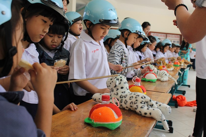 Students at Truong Dinh Primary School playing a game as part of many activities to raise their awareness of wearing helmets while driving motorbikes. Photo: Minh Hung