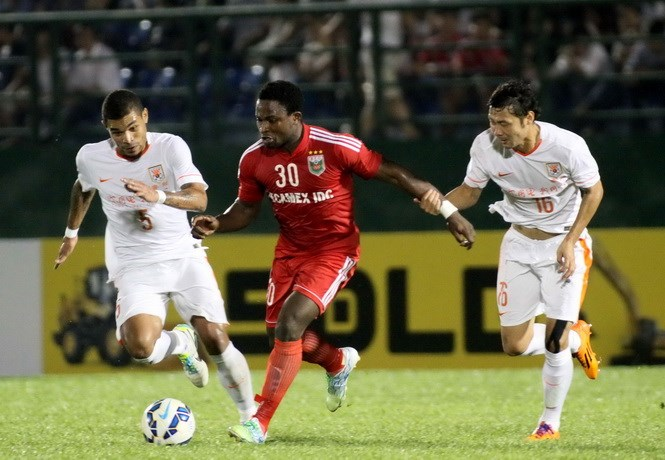 Becamex Binh Duong's Oseni (C) vies for the ball with two Shandong Luneng players during an AFC Champions League's Group E match in Binh Duong on Tuesday. Photo: Khả Hòa