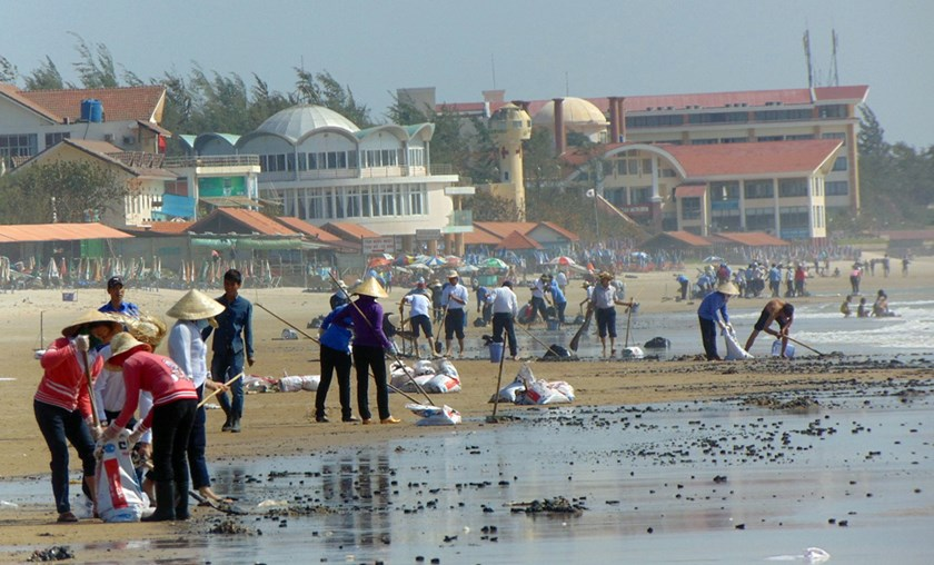People clean up oil sludge on Vung Tau Beach. Photo: Nguyen Long