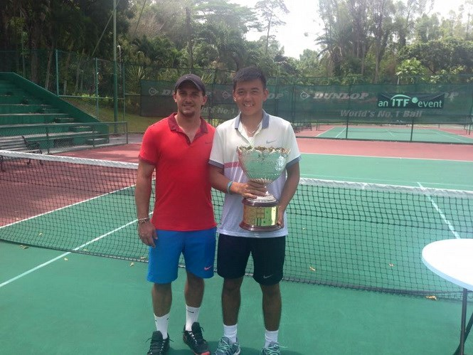 Ly Hoang Nam, 18, holds the cup as he poses for a photo with his Swedish coach Christian Brydniak.