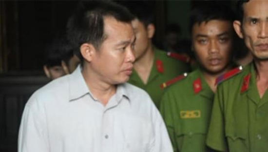 Phan Thanh Hoang, 36, is escorted out of the trial on March 30. Photo credit: CAND