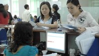 An employee of a social insurance agency in Ho Chi Minh City files paperwork for clients. Photo: Diep Duc Minh