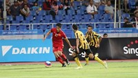 Vietnam's Mac Hong Quan (L) vies for the ball with two Malaysian players in a SEA Games match in Singapore on June 2, 2015.
