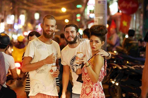 Foreign tourists celebrate the new year of 2015 with a local beer in downtown Ho Chi Minh City. Photo: Dao Ngoc Thach