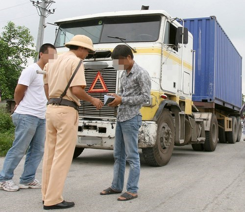 A container truck driver is pulled over on a highway in Hanoi. Photo: Ngoc Thang
