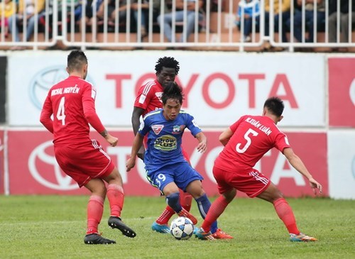 Hoang Anh Gia Lai's 18-year-old striker Nguyen Lam vies for the ball with three Becamex Binh Duong players. Photo: Thanh Nien