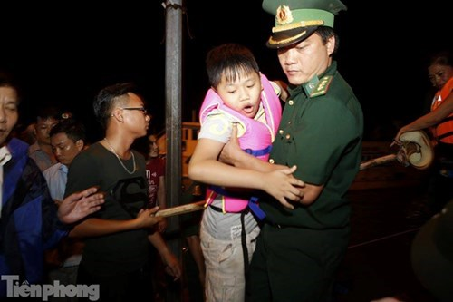 A soldier helps a boy get ashore after being stranded on Co To Island in Quang Ninh Province due to bad weather since July 26. Photo credit: Tien Phong