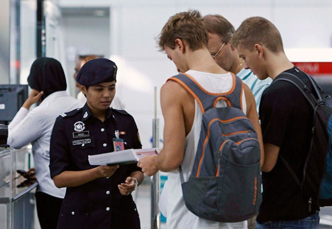 A Malaysian immigration officer checks papers of foreign passengers in Kuala Lumpur. Photo credit: Reuters