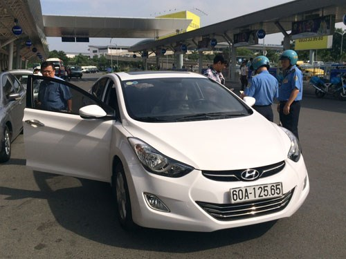 Traffic inspectors check an Uber car at Tan Son Nhat Airport in Ho Chi Minh City. Photo: Dinh Muoi