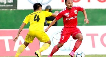 Becamex Binh Duong's Trong Hoang (R) vies for the ball against Thanh Hoa's Tran Tan Dat.