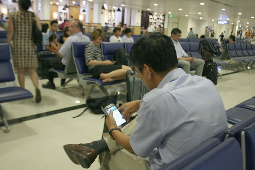 A man reads news on a smartphone at Ho Chi Minh City's Tan Son Nhat International Airport. Mobile Internet speed in Vietnam is the lowest in Southeast Asia, according to a recent report. Photo: Minh Hung