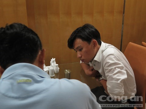 Dao Huy Hoang (R) speaks to a police officer. Photo credit: Cong an Thanh Pho Ho Chi Minh