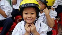 A primary school student in Dong Nai Province wears a helmet donated by Johnson & Johnson through Asia Injury Prevention Foundation's Helmets for Kids program. Photo: Minh Hung