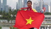 Truong Thi Phuong holds the national flag after winning a gold medal at the 28th Southeast Asian Games in June 2015 in Singapore. Photo: Tam Lan