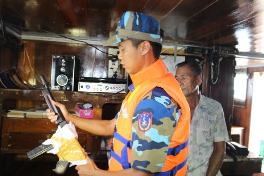 A Vietnamese coast guard inspects a gun on the Thai ship. Photo credit: Vietnam Coast Guard