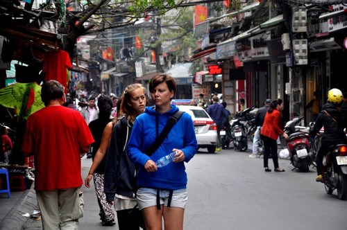 Tourists stroll down a street in downtown Hanoi. Photo: Ngoc Thang